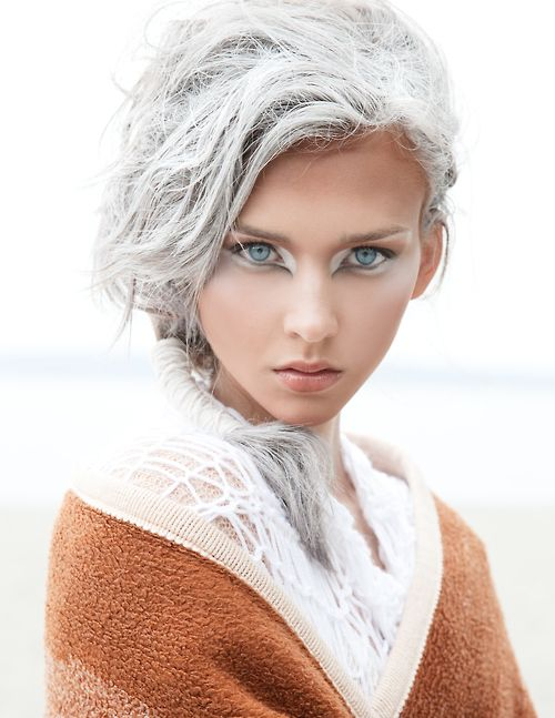White eyeshadow creating a stunning visual effect around the piercing blue eyes,...